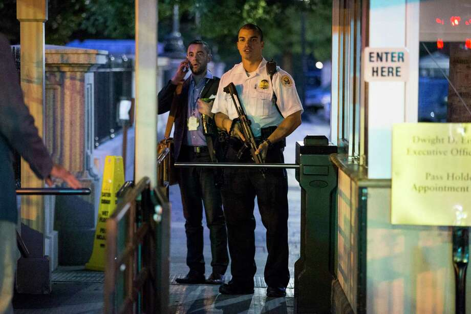 A Secret Service police officer holds a weapon as he stands near an entrance to the White House complex during an evacuation minutes after President Barack Obama departed Washington for Camp David aboard Marine One on Sept. 19, 2014. A Secret Service agent at the scene says someone jumped the fence surrounding the White House. Photo: AP Photo/Evan Vucci  / AP