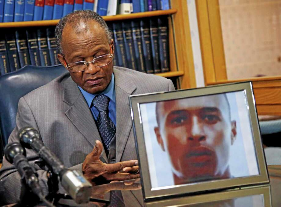 Salvadore Furtado listens during a news conference at his attorney's office in Quincy, Massachusetts, on Thursday with a photo of his son, Safiro Furtado. Safiro and Daniel de Abreu were shot to death as they sat in a car in Boston's South End on July 16, 2012. Former New England Patriots tight end Aaron Hernandez, who already faces a murder charge in a man's shooting death last year, was indicted on new murder charges in this 2012 double slaying in Boston. Photo: Elise Amendola — The Associated Press  / AP