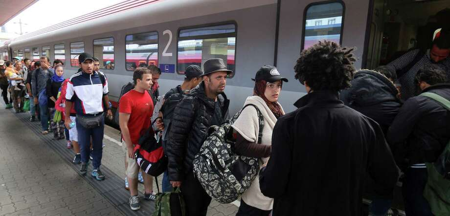 Migrants and refugees board  a train from Vienna to Salzburg at the Westbahnhof train station in Vienna Saturday. Photo: Associated Press  / AP