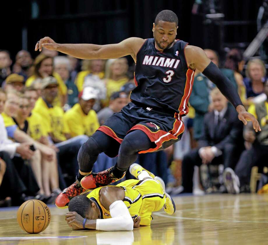 Miami Heat guard Dwyane Wade goes over Indiana Pacers forward Paul George as they go after a loose ball during the fourth quarter of Game 2 of the Eastern Conference finals Tuesday night in Indianapolis. Photo: Michael Conroy — The Associated Press  / AP