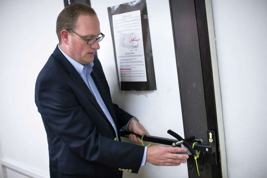 In this file photo taken July 20, Ben Richards, principal of Watkins Memorial High School, demonstrates the use of a security device in Pataskala, Ohio. Photo: Associated Press  / AP
