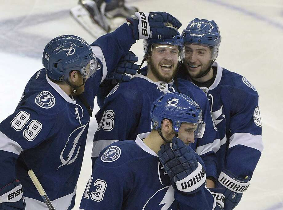 Lightning right wing Nikita Kucherov (86) celebrates with teammates, including defenseman Nikita Nesterov (89) and center Tyler Johnson (9) after scoring the game-winning goal against the New York Rangers during the overtime period of Game 3 of the Eastern Conference finals. Photo: Phelan M. Ebenhack — The Associated Press  / FR121174 AP