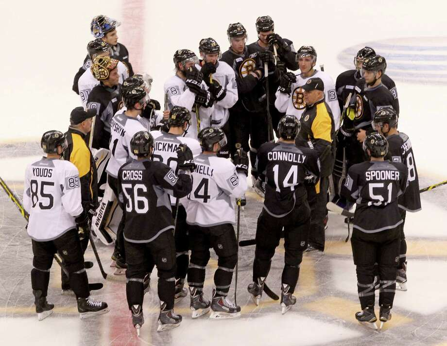Boston Bruins head coach Claude Julien talks to the team as they gather at center ice on the first day the full team skated during training camp on Friday. Photo: Mary Schwalm — The Associated Press  / FR158029 AP