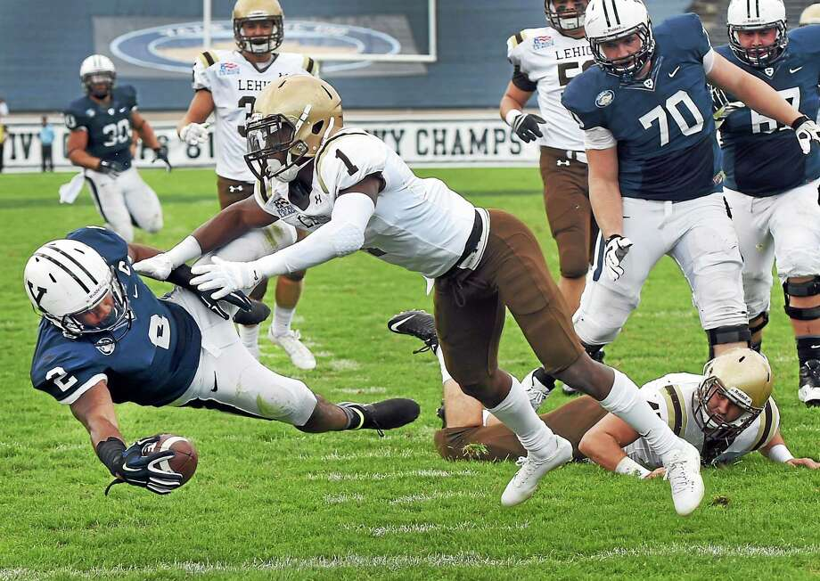 Yale's Deon Randall scores a touchdown after getting by Lehigh's Oliver Rigaud during the first quarter of the Bulldogs' 54-43 win on Saturday at Yale Bowl. Photo: Peter Hvizdak — Register  / ©2014 Peter Hvizdak