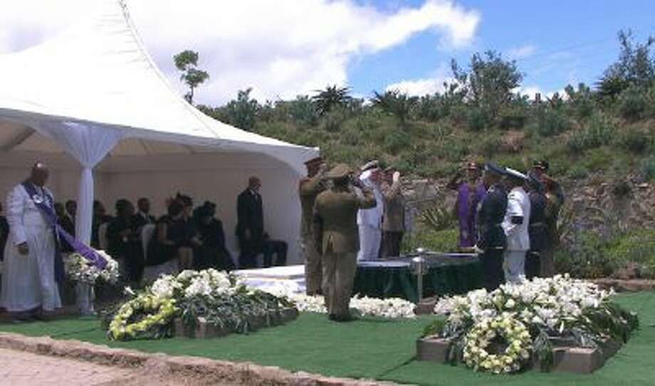 Mandela family members watch and military officers salute as former South African President Nelson Mandela's casket is lowered into his burial site following his funeral service in Qunu, South Africa, Sunday, Dec. 15, 2013.