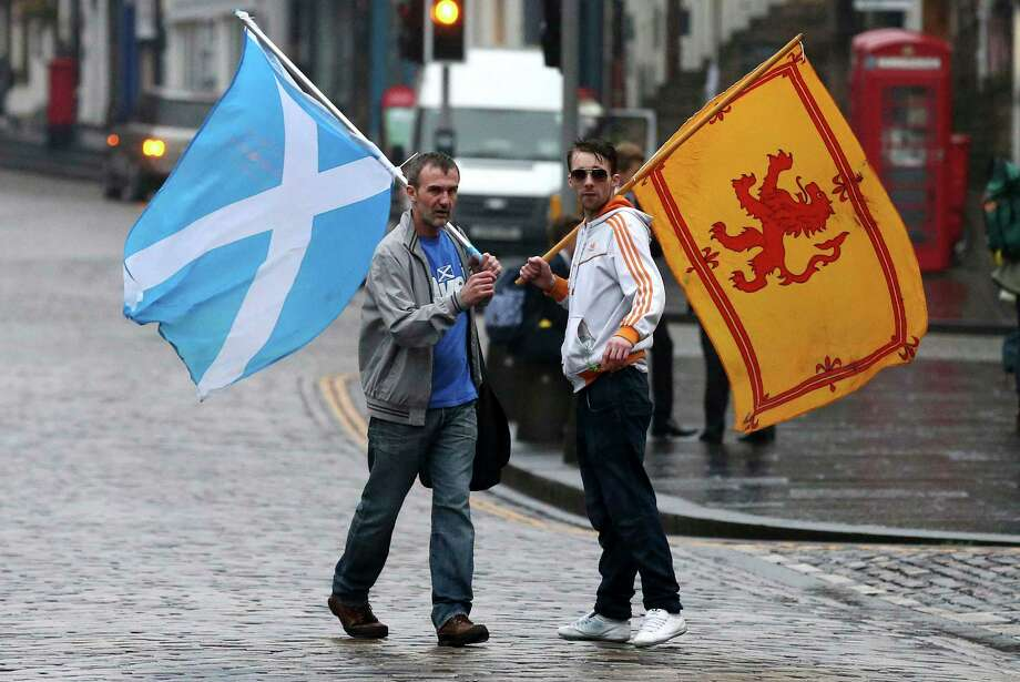 Supporters of the Yes campaign for the Scottish independence referendum stand Friday on the Royal Mile in Edinburgh, Scotland. Scottish voters have rejected independence and decided that Scotland will remain part of the United Kingdom. The result announced early Friday was the one favored by Britain's political leaders, who had campaigned hard in recent weeks to convince Scottish voters to stay. It dashed many Scots' hopes of breaking free and building their own nation. Photo: Associated Press  / AP