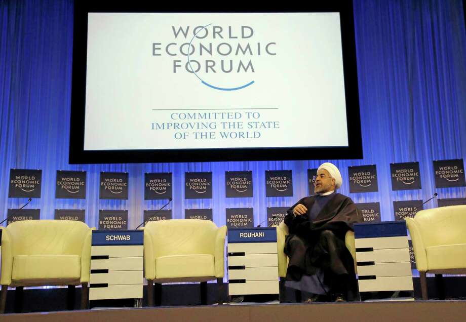 Iranian President Hassan Rouhani is listening to the welcome remarks during a session of the World Economic Forum in Davos, Switzerland, Thursday, Jan. 23, 2014. Leaders gathered in the Swiss ski resort of Davos have made it a top priority to push to reshape the global economy and cut global warming by shifting to cleaner energy sources. (AP Photo/Michel Euler) Photo: AP / AP