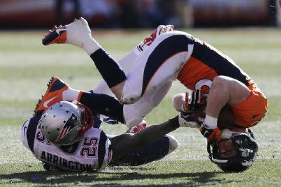 Denver Broncos wide receiver Wes Welker (83) is upended by New England Patriots cornerback Kyle Arrington (25) during the AFC Championship Game.