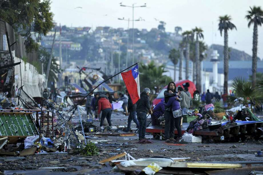 A couple embraces in the middle of a debris strewn street on Sept. 17, 2015, where a Chilean flag was placed after an earthquake-triggered tsunami hit Coquimbo, Chile. Photo: Aton Chile, Alejandro Pizarro Via AP  / Agencia Aton Chile