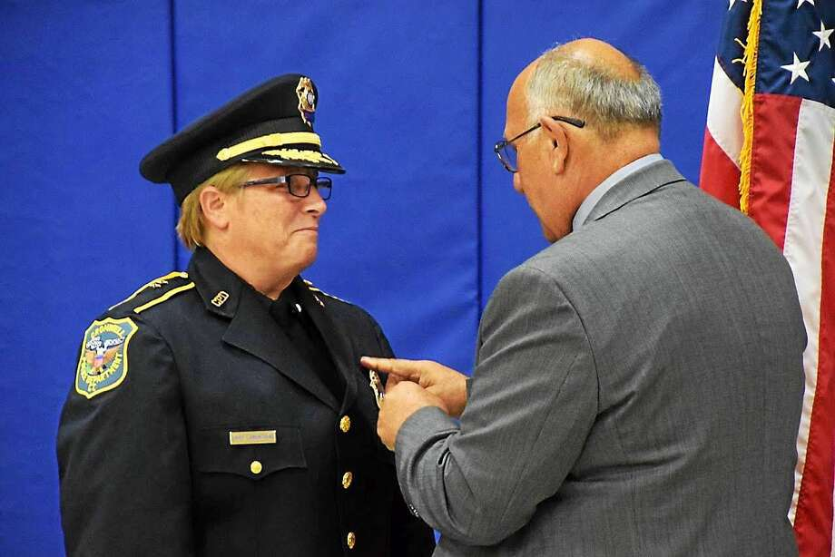Cromwell Town Manager Anthony Salvatore, right, pins his successor, Police Chief Denise Lamontagne. Photo: Journal Register Co.