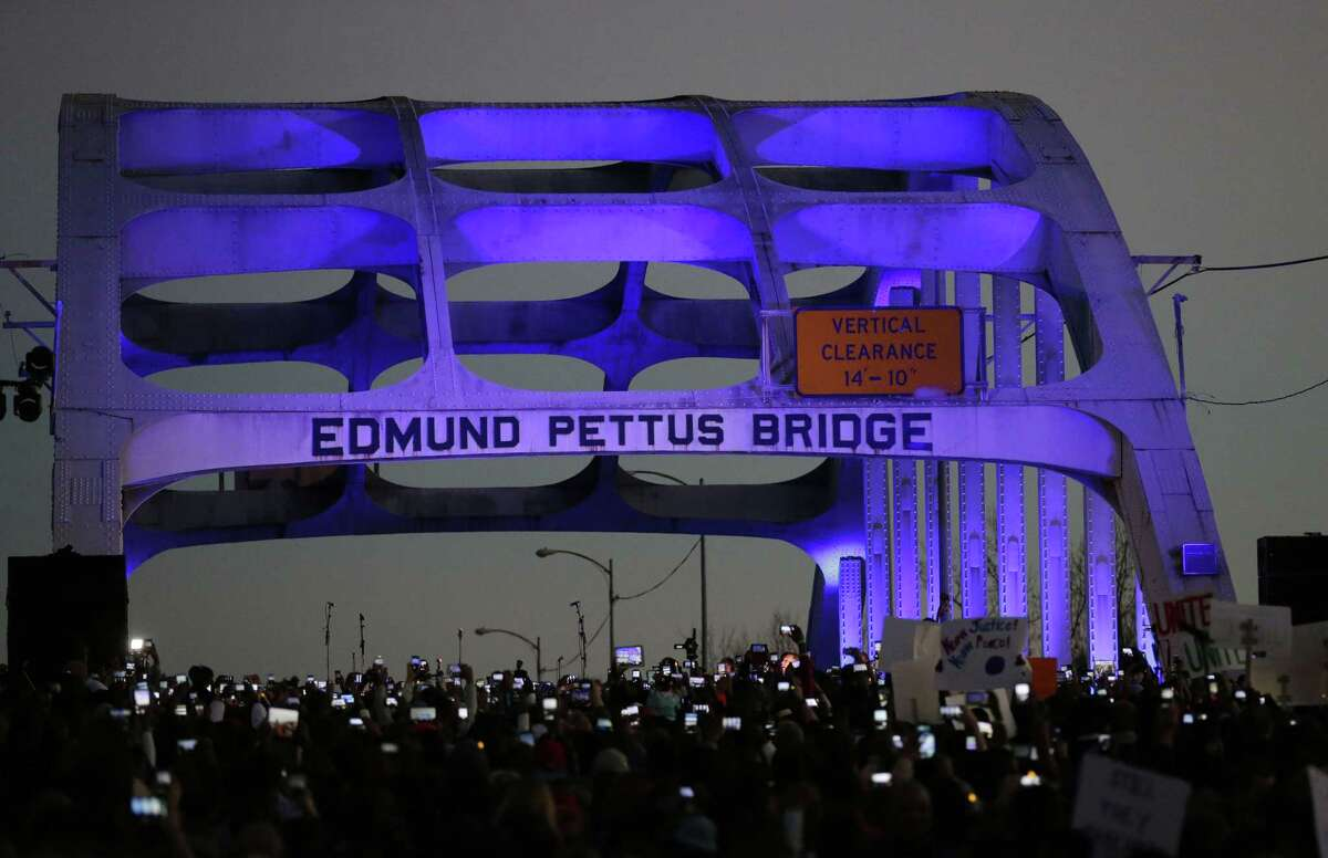 In this Jan. 18, 2015 file photo, marchers hold up a their cellular phones to record the rapper Common and singer songwriter John Legend perform at the foot of the Edmund Pettus Bridge in honor of Martin Luther King Jr., in Selma, Ala.