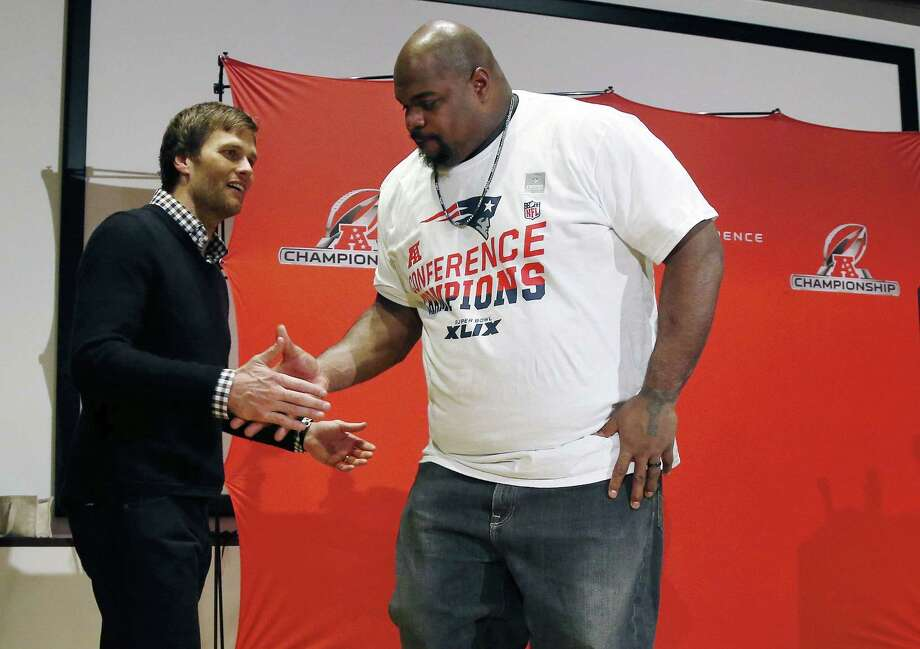 Patriots quarterback Tom Brady, left, shakes hands with defensive lineman Vince Wilfork during a press conference after Sunday's AFC Championship game. Photo: The Associated Press  / AP