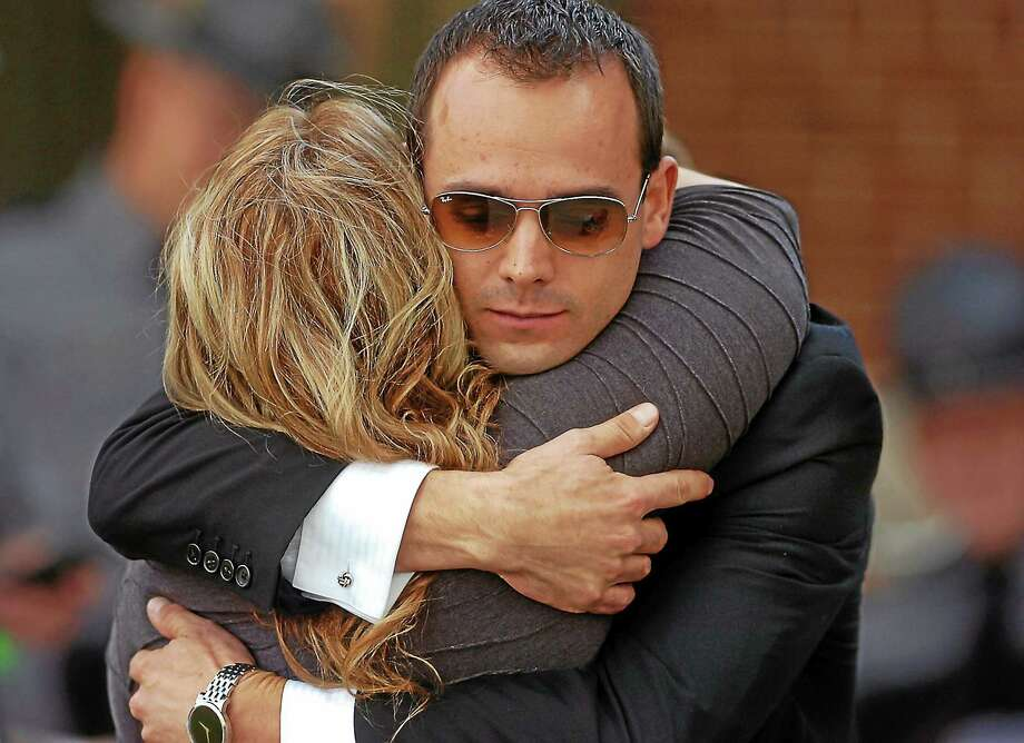 A man and woman embrace after leaving the Rotunda for the viewing of Pennsylvania State Trooper Cpl. Bryon Dickson on Sept. 17, 2014, at Marywood University in Scranton, Pa. Photo: AP Photo/The Scranton Times-Tribune, Butch Comegys  / The Scranton Times-Tribune