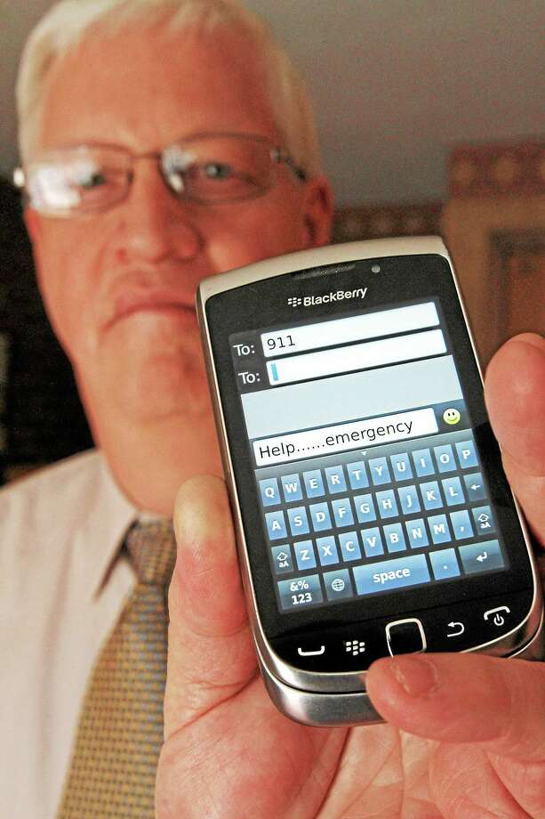 In this April 18, 2012 photo, David Tucker, executive director of Vermont's Enhanced 911 Board, holds a smartphone in Montpelier, Vt. Tucker says the state is the first in the country where customers of the four major wireless carriers can send text messages to 911. As of Monday, May 19, 2014, T-Mobile customers in Vermont are now able to text 911. Verizon, AT&T and Sprint began the service earlier. Photo: AP Photo/Toby Talbot, File  / AP