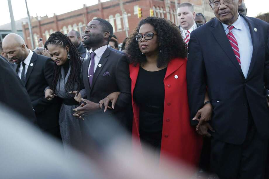 """Oprah Winfrey locks arms with David Oyelowo, left, who portrays Martin Luther King Jr. in the movie """"Selma,"""" Ava DuVernay, the director of """"Selma"""" and rapper Common, far left, as they march to the Edmund Pettus Bridge in honor of Martin Luther King Jr. on Jan. 18, 2015, in Selma, Ala. Photo: AP Photo/Brynn Anderson  / AP"""