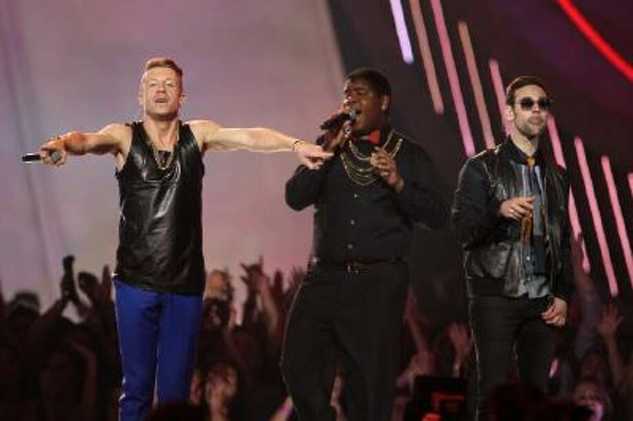 "This April 14, 2013 file photo shows Macklemore, left, and Ryan Lewis, right, performing ""Can't Hold Us"" with Ray Dalton at the MTV Movie Awards in Sony Pictures Studio Lot in Culver City, Calif."