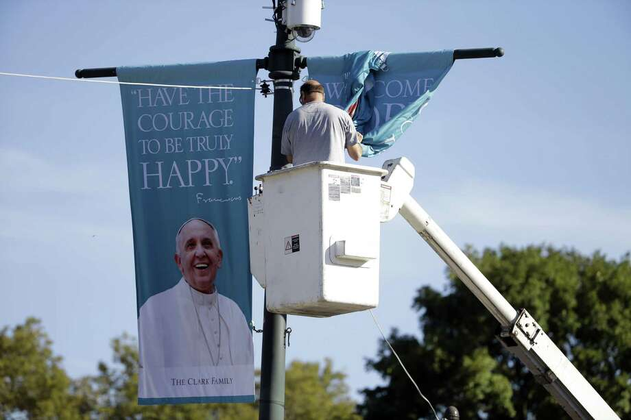 A worker hangs banners on Sept. 16, 2015, ahead of Pope Francis' scheduled visit on the Benjamin Franklin Parkway in Philadelphia. Photo: AP Photo/Matt Rourke  / AP