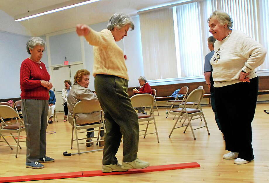 Shirley Ristau, right, coaches Johanna O'Neill, center, through a balance obstacle course while O'Neill's sister, Mary O'Neill, left, looks on during a fall prevention demonstration class at the Manchester Senior Center in Manchester, Conn. Photo: AP Photo/Jessica Hill