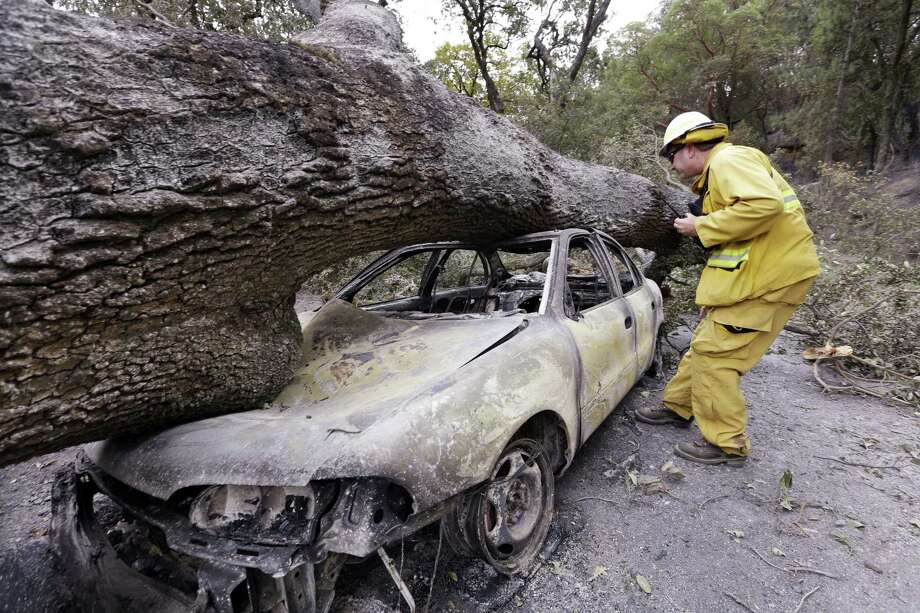 Firefighter Jeff Ohs looks into a burned out car on Sept. 15, 2015 that was also hit by a tree at the Harbin Hot Springs resort in a wildfire several days earlier near Middletown, Calif. The fire that sped through Middletown and other parts of rural Lake County, less than 100 miles north of San Francisco, has continued to burn since Saturday despite a massive firefighting effort. Photo: AP Photo/Elaine Thompson  / AP