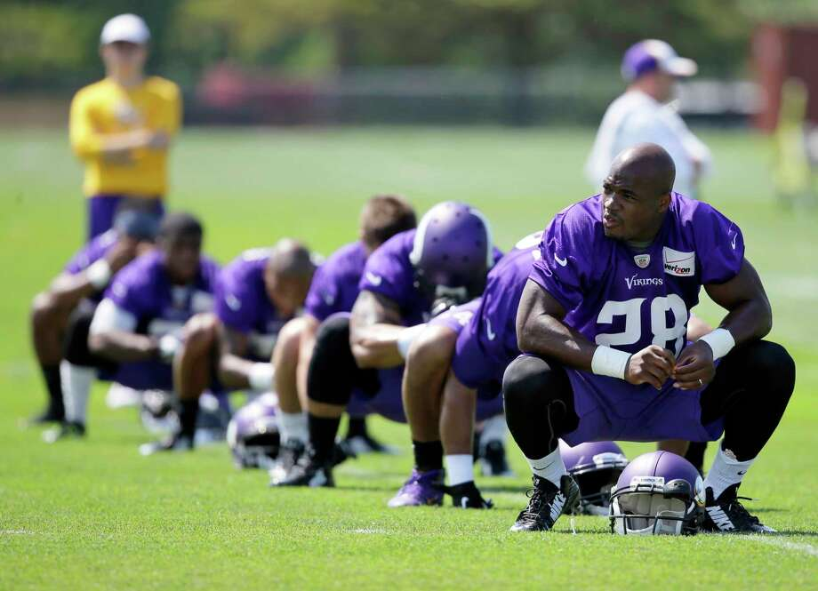 Minnesota Vikings running back Adrian Peterson (28) stretches during training camp in July in Mankato, Minn. Photo: Charlie Neibergall — The Associated Press File Photo  / AP
