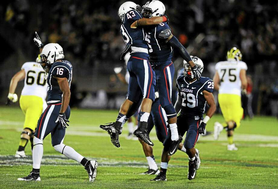 UConn cornerback Jhavon Williams celebrates with running back Lyle McCombs (43) after intercepting a pass against Michigan last September at Rentschler Field in East Hartford. Photo: Jessica Hill — The Associated Press File Photo  / FR125654 AP