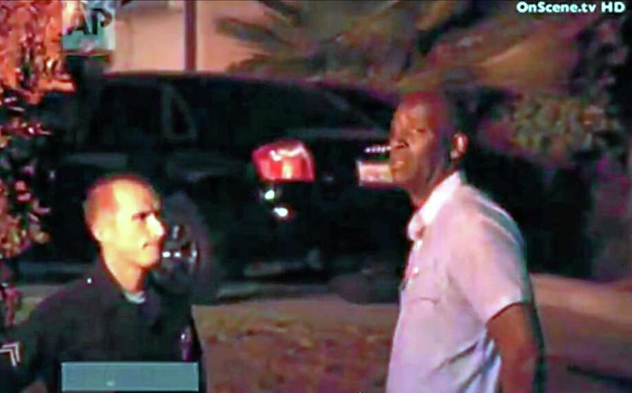 "In this image taken from video from OnScene.tv, actor Michael Jace, right, is detained by police outside his home in Los Angeles on Monday night, May 19, 2014. Jace, who played a police officer on the hit TV show ""The Shield,"" was arrested on suspicion of homicide after his wife was found shot to death in their Los Angeles home, authorities said. (AP Photo/OnScene.tv) Photo: AP / OnScene.tv"