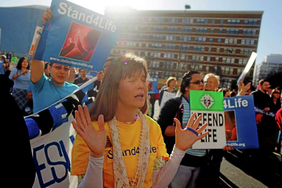 Geri Doyle raises her hands in worship during a musical performance at the Dallas March for Life & Rally Saturday, Jan. 18, 2014 in downtown Dallas. Thousands attended the event, which marked the 41st anniversary of Roe v. Wade. (AP Photo/The Dallas Morning News, G.J. McCarthy) MANDATORY CREDIT Photo: AP / The Dallas Morning News