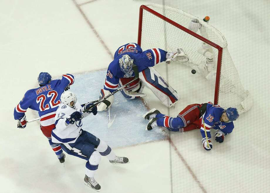 Rangers goalie Henrik Lundqvist (30) and right wing Martin St. Louis (26) slide into the goal as the puck hits the back of the net for a goal by Lightning center Tyler Johnson in the first period on Monday. Photo: Julie Jacobson — The Associated Press  / AP