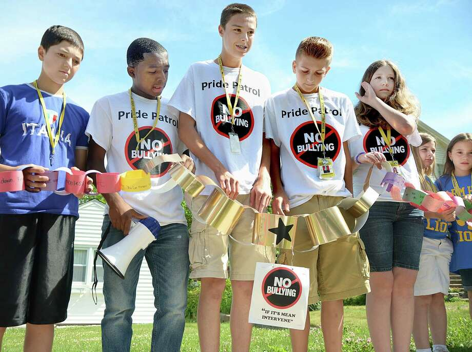 In this file photo from June, Woodrow Wilson seventh-grader Garrett Pellici and eighth-graders and members of the Ram Pride Patrol Jay Hoggard, Sean Lenehan, Carson Fitzner and Nicole Badamo hold the gold links that connect the anti-bullying message from the Ram Pride Patrol in Middletown. Photo: Catherine Avalone - The Middletown Press