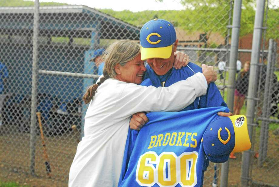 Haddam-Killingworth baseball coach Mark Brookes gets a hug from his wife, Rae, following his 600th career win on Sunday. Photo: Jimmy Zanor — Middletown Press