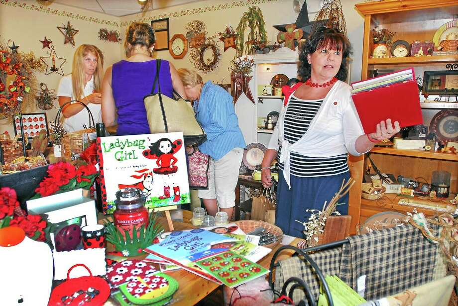MARC Community Resources CEO and President Liz Warner talks with a friend at Ladybug Boutique at 122 College Street in Middletown in this file photo from 2012. Photo: Catherine Avalone | The Middletown Press File Photo  / a