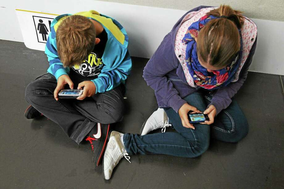 Children play video games on smartphones. An October workshop for Cromwell parents will identify possible dangers posed when young ones use the Internet. Photo: File Photo  / 2012 Getty Images