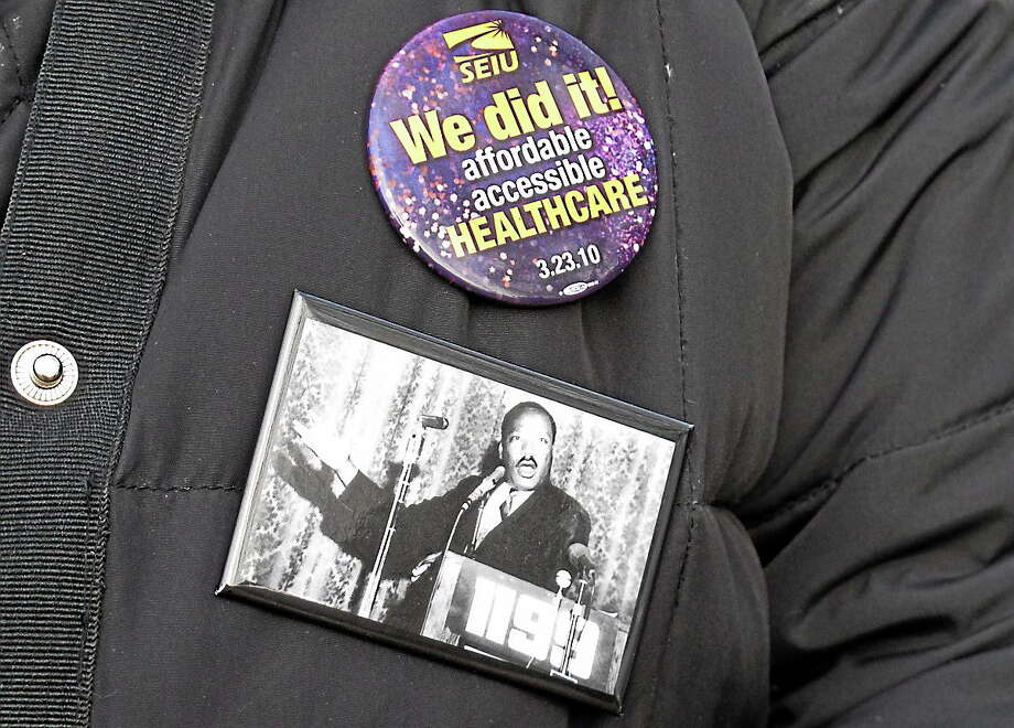 A striking nursing home worker wears buttons on her coat during a rally in Newington, Conn. on Dec. 12, 2012. Photo: AP Photo/Dave Collins  / AP
