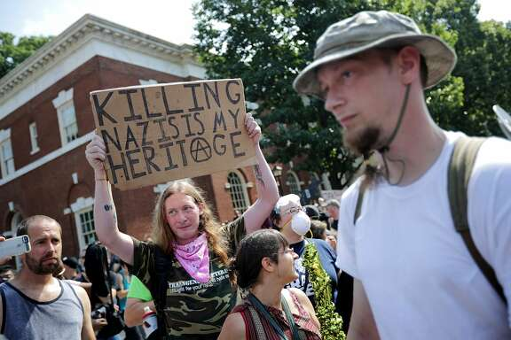 "CHARLOTTESVILLE, VA - AUGUST 12:  Counter-protesters line the route taken by white nationalists, neo-Nazis and members of the ""alt-right"" during the ""Unite the Right"" rally August 12, 2017 in Charlottesville, Virginia. After clashes with anti-fascist protesters and police the rally was declared an unlawful gathering and people were forced out of Lee Park, where a statue of Confederate General Robert E. Lee is slated to be removed.  (Photo by Chip Somodevilla/Getty Images)"