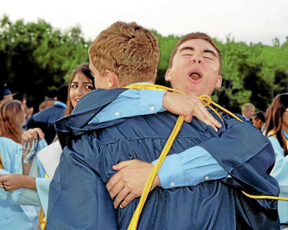 Sandy Aldieri/Special to the Press/Drew Cietek hugs friend, Chris Polson, while fellow classmate Fatima Bishtawi looks on as graduates celebrated after the Middletown High graduation ceremonies on Friday. Photo: Journal Register Co.