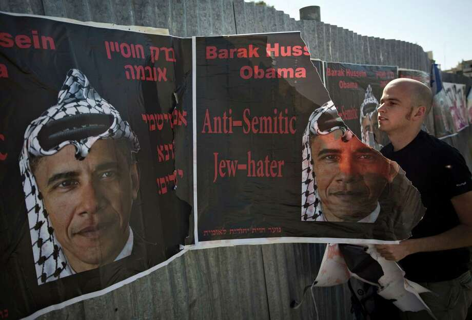 In this June 14, 2009, photo, an Israeli man tears posters hung by an extremist right wing group, depicting U.S. President Barack Obama, wearing a traditional Arab headdress, in Jerusalem. Seeking to sell his nuclear deal with Iran to a skeptical Israeli public, Obama has repeatedly declared his deep affection for the Jewish state. Photo: Sebastian Scheiner — The Associated Press  / AP