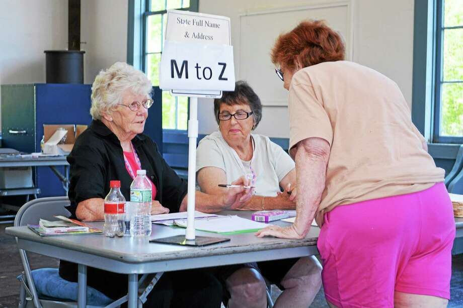 Catherine Avalone - The Middletown Press East Haddam resident Joanne Roczniak checks in with poll workers Nancy Cummings, at left and Louise Pear to vote during East Haddam's budget vote Tuesday afternoon at the Old Town Hall on Town Street in East Haddam. Photo: Journal Register Co.