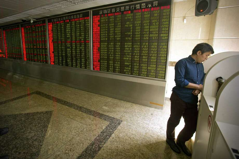 A Chinese investor uses a computer terminal to monitor stock prices at a brokerage house in Beijing on Sept. 15, 2015. World stock markets were lower Tuesday after China's benchmark suffered a late session sell-off and the Bank of Japan kept its monetary policy unchanged ahead of a much anticipated U.S. Federal Reserve decision later this week on whether to raise interest rates. Photo: AP Photo/Mark Schiefelbein  / AP