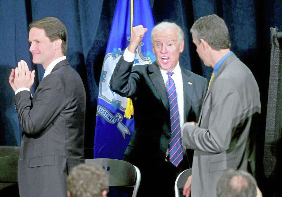 U.S. Rep. Chris Himes (left) applauds as Vice President Joe Biden (center) raises his fist as he exits the Campus Center Ballroom at Western Connecticut State University in Danbury after speaking at a Conference on Gun Violence on 2/21/2013. U.S. Secretary of Education Arne Duncan is at right. ¬ Photo by Arnold Gold/New Haven Register Photo: Journal Register Co.