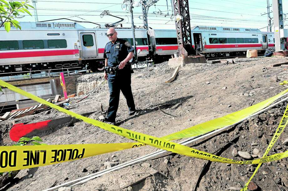 MTA Police Officer Victor Pastrana walks by the scene of a Metro North train derailment in Bridgeport near the Fairfield line on 5/18/2013.  Behind him is the southbound train involved in the accident. ¬ Photo by Arnold Gold/New Haven Register Photo: Journal Register Co.