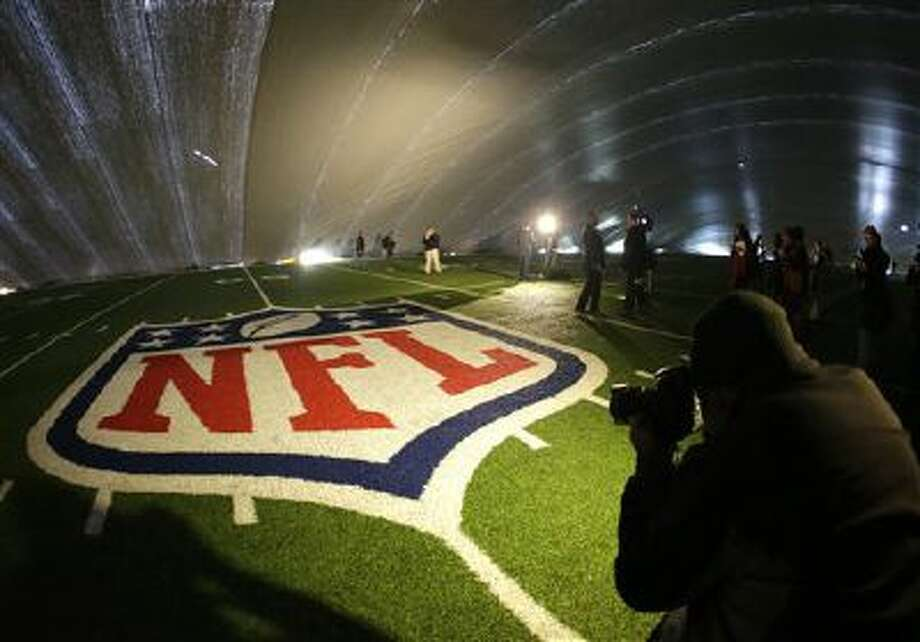 The NFL logo at midfield of MetLife Stadium is illuminated by lights on television reporters' videocameras as members of the media are given a tour under a tarp used by crews to keep the turf dry ahead of Super Bowl XLVIII, Wednesday, Jan. 15, 2014, in East Rutherford, N.J. Among other preparations, crews are setting up a perimeter 300 feet from the entrances to the stadium as a security measure. Photo: AP / AP