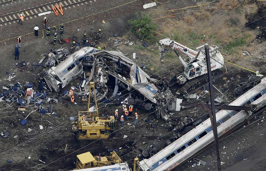 In this aerial photo taken May 13, 2015, emergency personnel work at the scene of a deadly train wreck in Philadelphia. Amtrak faces what probably will be a $200 million payout to crash victims -- the cap established by Congress nearly 20 years ago as part of a compromise to rescue the railroad from financial ruin. Photo: AP Photo/Patrick Semansky  / AP