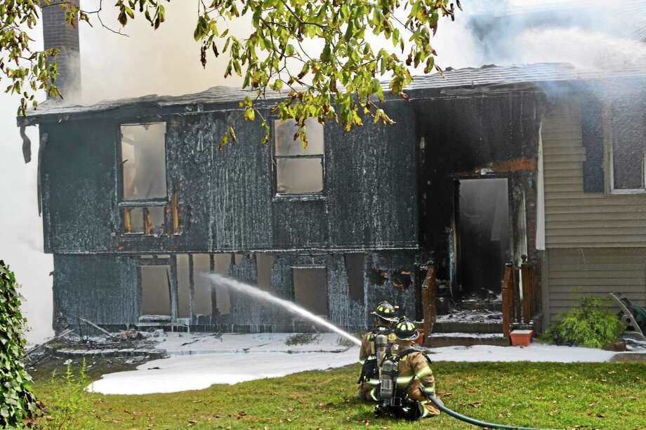 Kathleen Schassler - The Middletown Press A fire on Jackson Hill Road in Middletown touched off Tuesday just before noon. Here, Dan Quincy speaks to Middlefield fireman about an addition to his house. Photo: Journal Register Co.