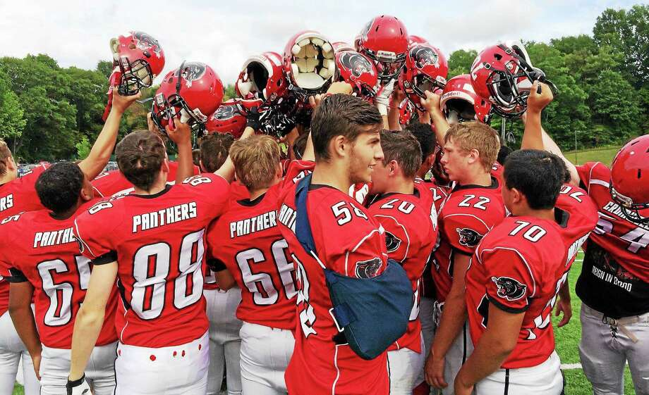 Cromwell/Portland's football team celebrates after beating Coginchaug 20-13 in its first game since drawing scrutiny for a hazing incident. Photo: Photo Sean Patrick Bowley -- GameTime CT