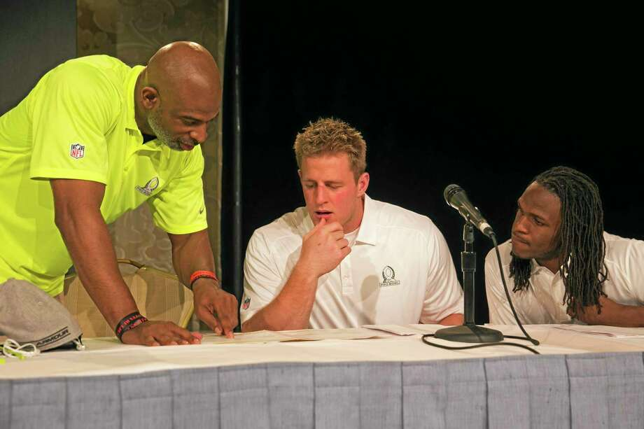 Hall of Famer Deion Sanders, left, goes over a Pro Bowl roster with Houston Texans defensive end J.J. Watt, center, and Kansas City Chiefs running back Jamaal Charles during a news conference for the Pro Bowl draft, which was held Tuesday in Kapolei, Hawaii. Photo: Marco Garcia — The Associated Press  / FR132415 AP