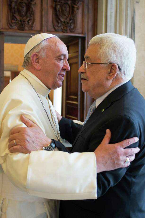 """Pope Francis greets Palestinian leader Mahmoud Abbas during an audience at the Vatican Saturday, May 16, 2015. Pope Francis has praised Palestinian President Mahmoud Abbas as an """"angel of peace"""" during a meeting at the Vatican. Francis made the compliment Saturday during the traditional exchange of gifts at the end of an official audience in the Apostolic Palace. (L'Osservatore Romano/Pool Photo via AP) Photo: AP / L'Osservatore Romano"""