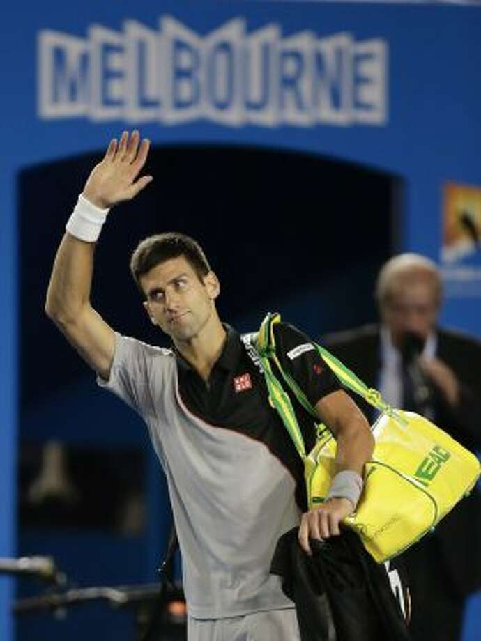 Novak Djokovic of Serbia waves to the crowd after losing his quarterfinal match against Stanislas Wawrinka of Switzerland at the Australian Open tennis championship in Melbourne, Australia, Tuesday, Jan. 21, 2014.