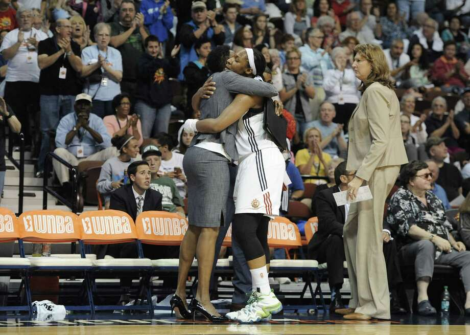 The Connecticut Sun's Kelsey Bone, center, hugs assistant coach Jennifer Gillom as fans applaud her and head coach Anne Donovan, right, after Bone left the game in the second half. Photo: Jessica Hill — The Associated Press  / FR125654 AP