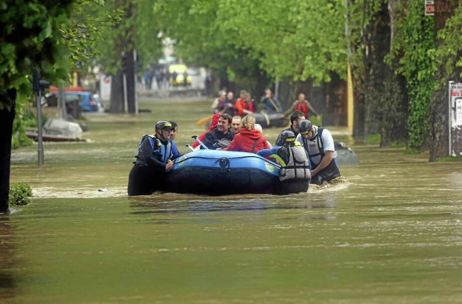 Members of the Bosnian Army rescue people from their flooded homes,  in the Bosnian town of Maglaj, 150 kms north of Sarajevo, Friday May 16, 2014. Two people drowned in Serbia and the country declared a national emergency Thursday as rain-swollen rivers across the Balkans flooded roads and bridges, shut down schools and cut off power. Hundreds of people had to be evacuated. In Serbia and neighboring Bosnia, meteorologists said the rainfall was the most since measuring started 120 years ago. Belgrade authorities say the average rainfall of a two-month period hit the city in just 40 hours. (AP Photo/Amel Emric) Photo: AP / AP