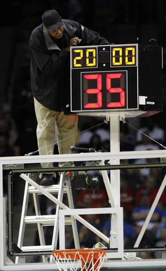 FILE - In this March 19, 2010, file photo,†a technician adjusts a shot clock after it malfunctioned and delayed the start of the California against Louisville NCAA first-round college basketball game in Jacksonville, Fla. The NCAA men's basketball rules committee completes this week's meetings by announcing its recommendations for changes Friday, May 15, 2015. They're expected to reduce the shot clock from 35 to 30 seconds and look for ways to speed up the end of games.(AP Photo/Steve Helber, File) Photo: AP / AP